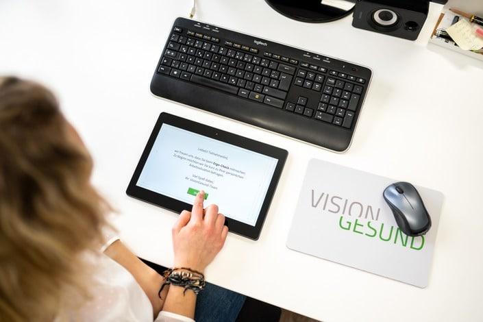 Im Mittelpunkt des Bildes liegt ein schwarzes Tablet, vor einer Computertastatur. Rechts daneben befindet sich eine Maus auf einem VisionGesund-MousePad. Der Kopf einer blonden Frau ist in der linken Bildhälfte zu erkennen: Sie tippt auf dem Tablet vor sich und trägt eine weiße Bluse.