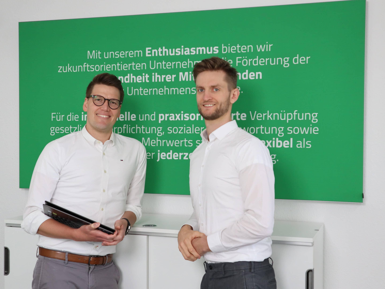 Die zwei Geschäftsführer von VisionGesund stehen vor einer grünen Wand und schauen freundlich ins Bild.