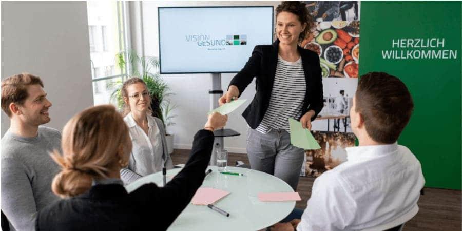 Die stehende VisionGesund-Expertin reicht einer Teilnehmerin der am Tisch sitzenden, vierköpfigen Arbeitsgruppe lächelnd einen bunten Zettel. Im Hintergrund sind Aufsteller des Unternehmens VisionGesund in dessen Farben Silber und Grün zu sehen. Die Stimmung wirkt entspannt, es herrscht eine angenehme Atmosphäre.