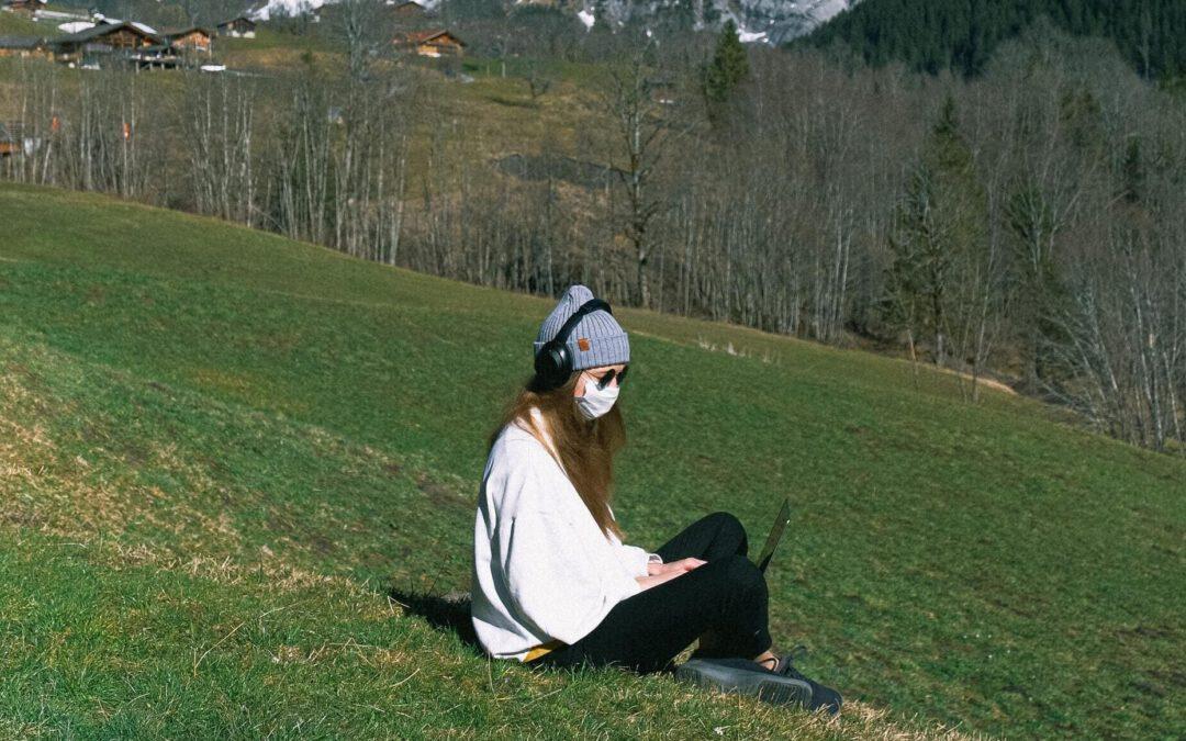 Eine junge Frau sitzt mit Maske und Mütze bekleidet im Schneidersitz auf dem Abhang einer Bergwiese. Sie trägt Kopfhörer und schaut auf den Bildschirm des Laptops auf ihrem Schoß. Im Hintergrund sind Ansätze des Gebirges und Almen zu erkennen.