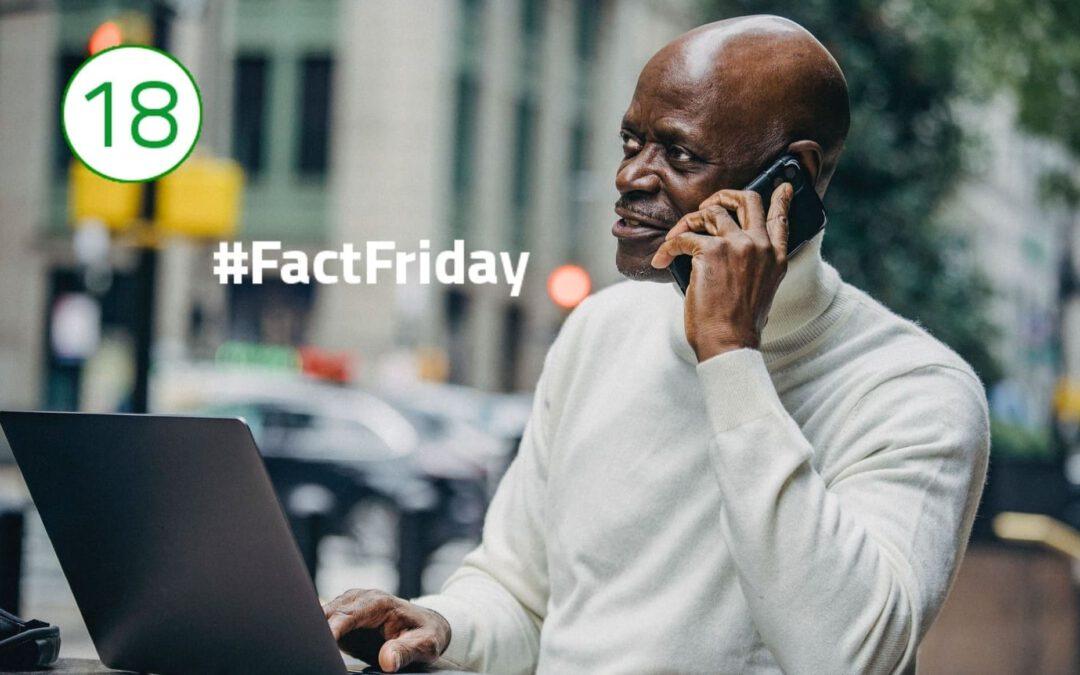 Ein Mann in weißem Rollkragenpullover telefoniert, während er vor einem Laptop sitzt und seine Hand auf der Tastatur abgelegt hat. Im Hintergrund ist Straßenverkehr zu sehen.