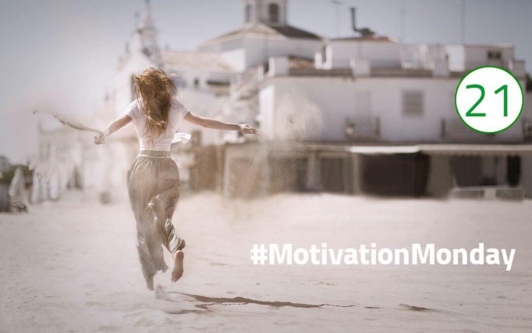 Eine Frau läuft mit ausgebreiteten Armen in einer weiten Haremshose und einem weißen Tshirt auf Sand an einem weißen Häuserkomplex vorbei. Der Sand weht hinter ihr auf, ihre langen braunen Haaren wehen ebenfalls im Wind. Das Bild vermittelt ein Gefühl von Freiheit und Glück.