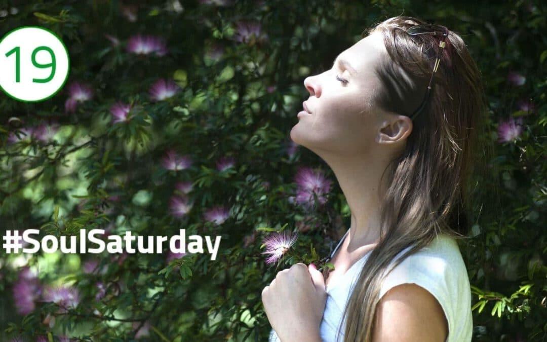 Eine Frau reckt mit geschlossenen Augen ihr Gesicht in die Sonne, die von der linken Bildseite einfällt. Im Hintergrund sind lila Blüten in einem Busch zu sehen, was dem Bild einen Ausdruck der Naturverbundenheit, Ruhe und Stille verleiht.
