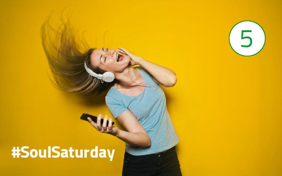 Eine Frau mit langen blonden Haaren trägt weiße Kopfhörer auf den Ohren, hält ein Smartphone in der rechten Hand und hält die linke Hand an das linke Ohr. Der Kopf ist nach oben geneigt, die Augen sind geschlossen und der Mund durch Singen geöffnet.