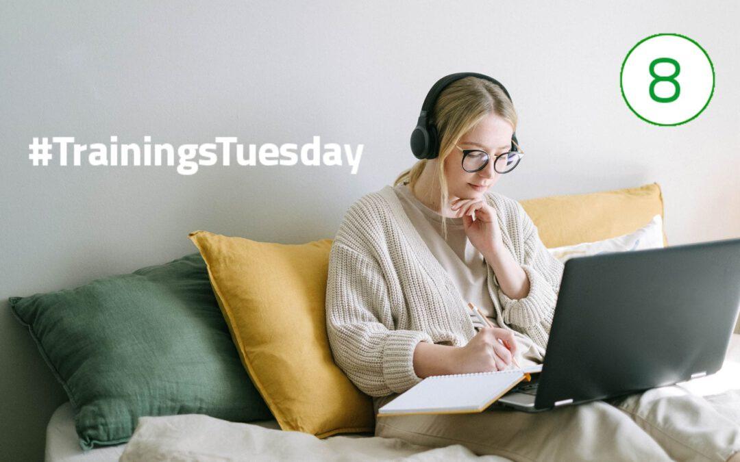 Eine junge Frau sitzt auf der Couch mit einem Laptop und Notizblock auf dem Schoß. Mit der rechten Hand schreibt sie etwas in den Notizblock und auf der linken Hand ist das Kind aufgestützt.