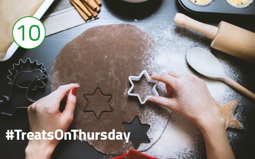 Ein dunkler Plätzchenteig liegt flach und kreisrund ausgerollt auf dem Tisch. Darauf werden kleine Sternchen ausgestochen, drumherum liegen verschiedene Backutensilien.