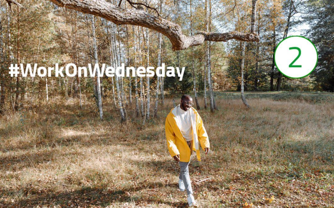 """Ein Mann mit offener, gelber Regenjacke spaziert durch den Wald und trägt ein Lächeln im Gesicht. Links im Bild steht """"#WorkOnWednesday"""" geschrieben und oben rechts im Bild ist die Zahl """"2"""" zu sehen."""