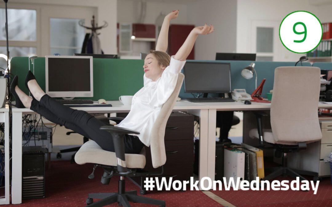 Frau mit weißer Bluse sitzt auf einem Bürostuhl am Schreibtisch, Füße auf dem Tisch und die Arme in die Höhe gestreckt.