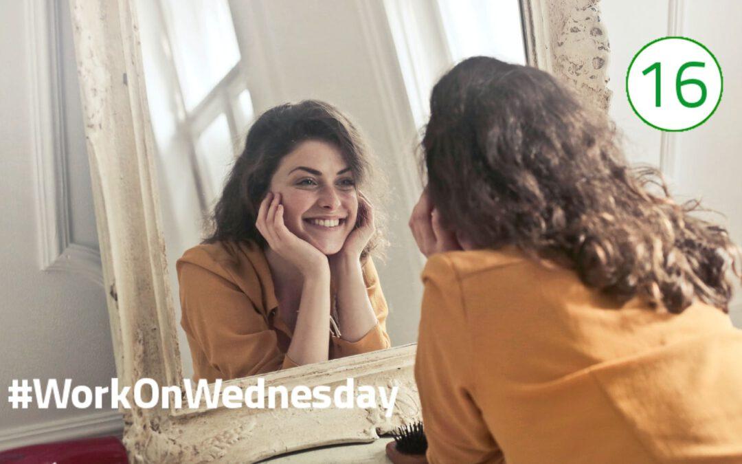 Eine Frau mit braunen Locken, bekleidet in einem orangen Pulli, lächelt ihr Spiegelbild an. Sie hat den Kopf auf ihre Hände gestützt und steht mit dem Rücken zur Kamera. Ihr Gesicht ist versetzt im Spiegelbild zu erkennen.