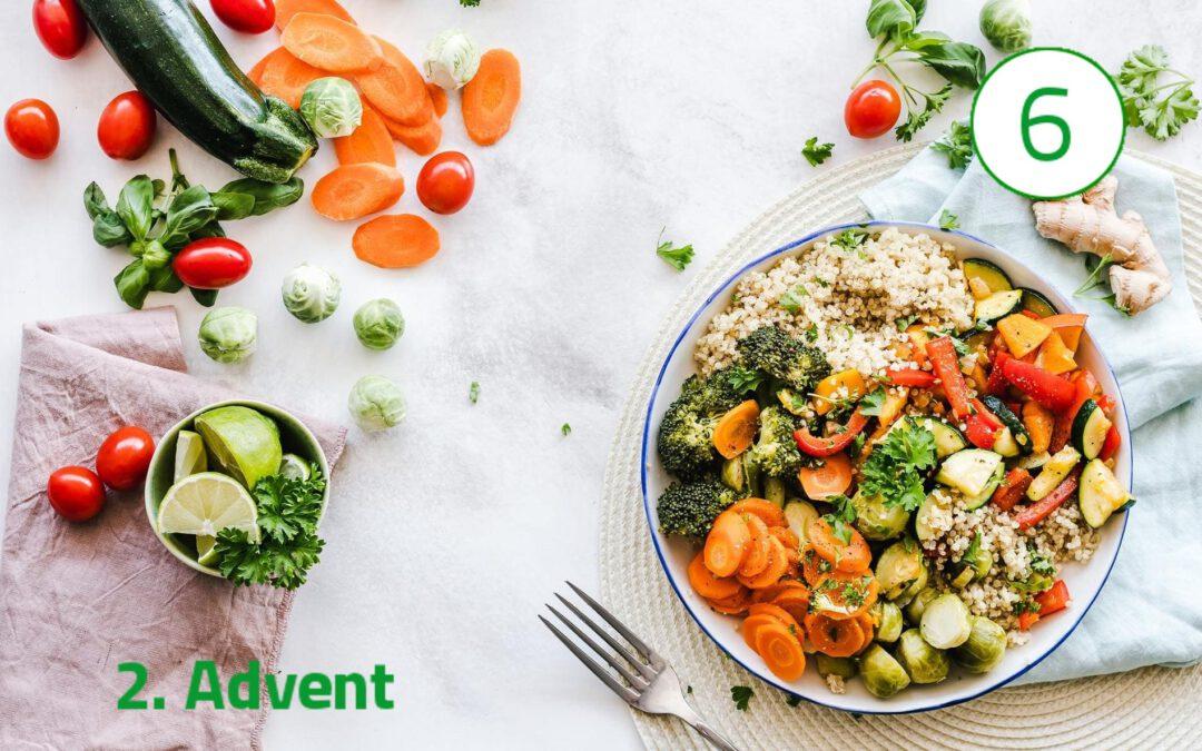 """Ein bunter Teller voller Gemüse ist auf der rechten Seite des Bildes zu sehen. Links unten steht """"2. Advent"""" geschrieben und darüber ist weiteres Gemüse wie Zuchini, Tomaten und Karotten."""